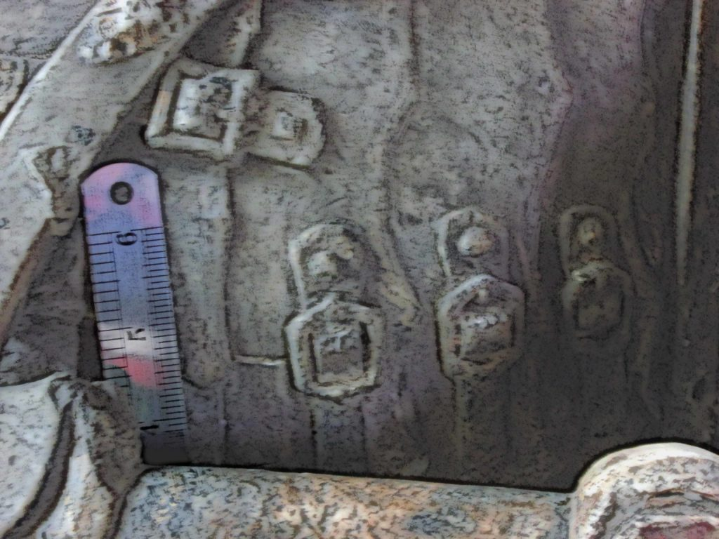Image of a four buckles depicted on a medieval tomb effigy.
