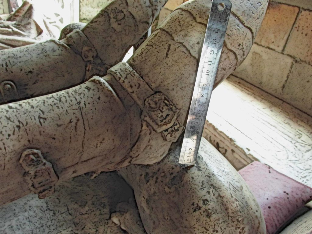 Image showing a buckle on the armoured foot of a medieval knight depicted in a tomb effigy.