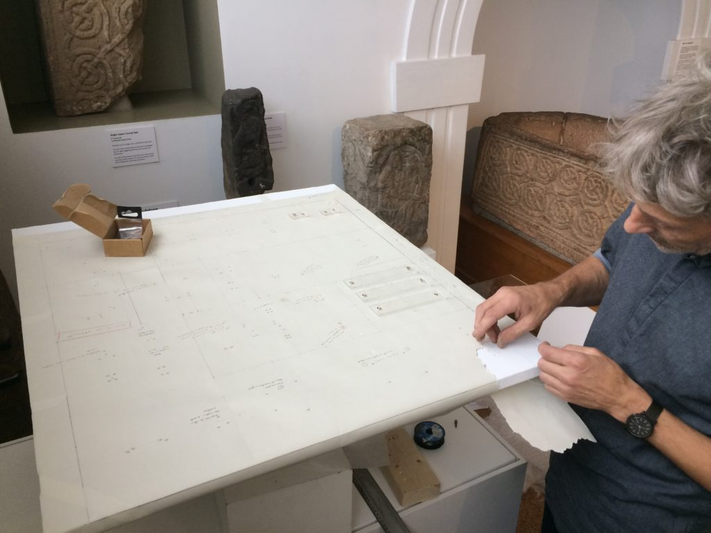 Rick Tailby, Facilitator and Technician at Derby Museums, planning the layout for the objects before mounting them.