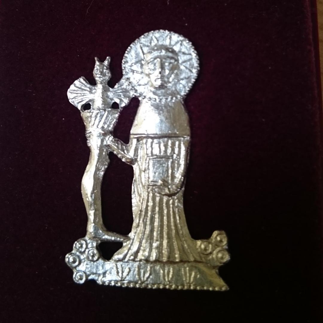 Image of a silver badge in the shape of a monk. In his left hand he holds a book and in his right hand he holds a long boot. A winged devil peeks out of the top of the boot.