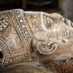 Image of a carved stone tomb effigy of a bishop. Close-up view of the head lying on pillow. The face has graffiti etched on it.