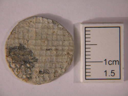 A resized image of Kent-DE15C3. Post Medieval. Token. Lead biface token square chequered field design. Obverse view.